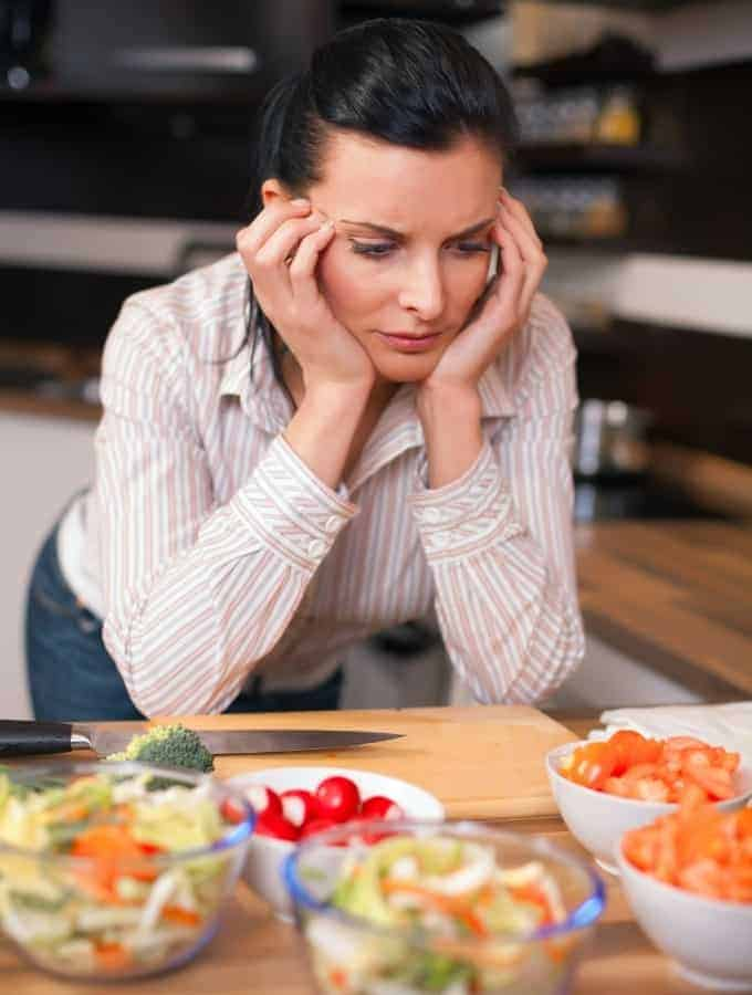 woman staring at food on a counter with a cutting board and knife in front of her