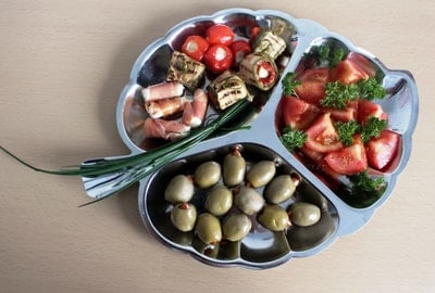 tray of olives, prosciutto wrapped cheese, tomatoes and other items