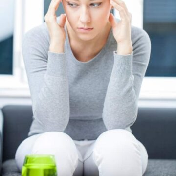 a woman holding her head in pain sitting on a couch