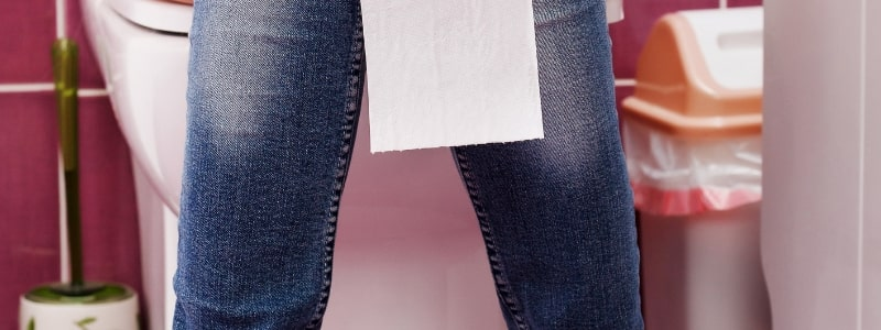 woman on the toilet with toilet paper hanging down