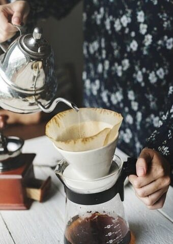 image of a woman pouring coffee into a pour-over coffee filter
