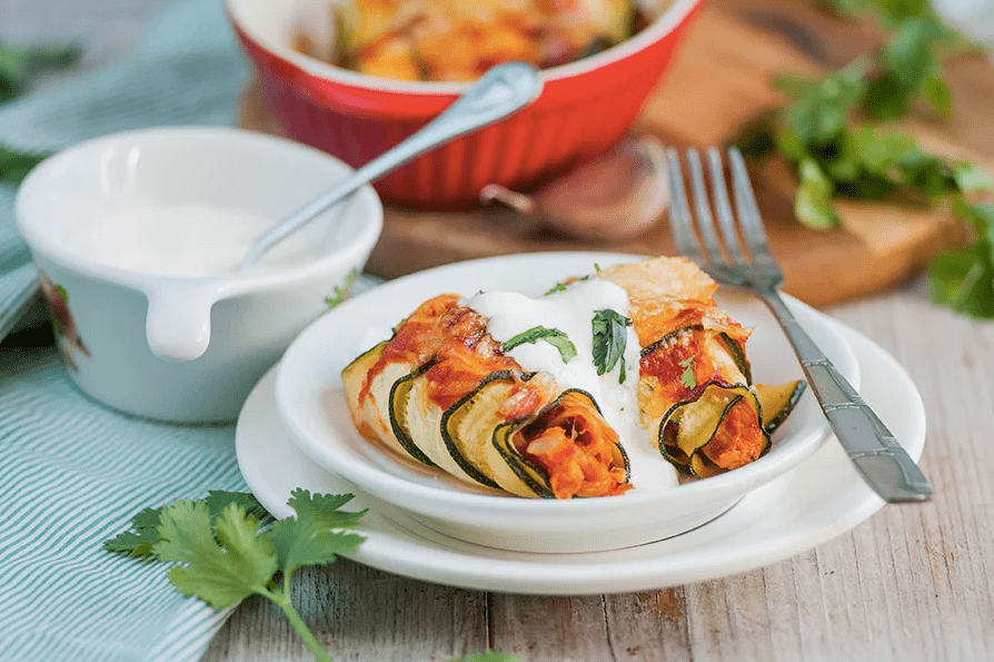 taco stuffed zucchini boats in a bowl with sour cream on top