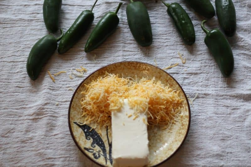 cream cheese and shredded cheese on a plate with jalapeños in front of the plate