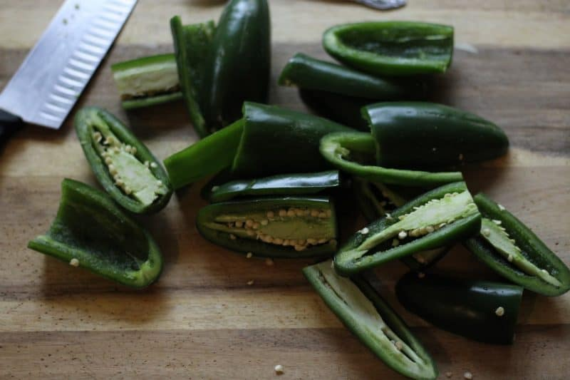 image of jalapenos cut in half on a cutting board