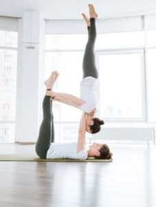 man and woman doing acro yoga together