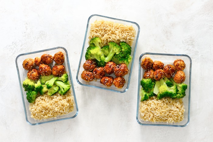 three meal prep containers with meat balls, brown rice and broccoli