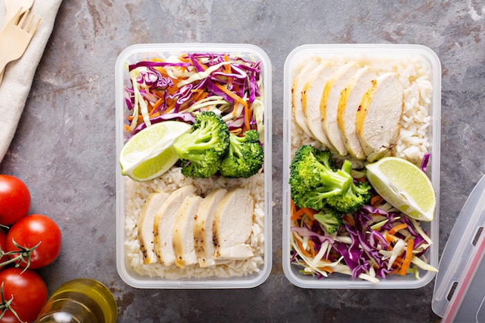 two meal prep containers with chicken, coleslaw, and rice