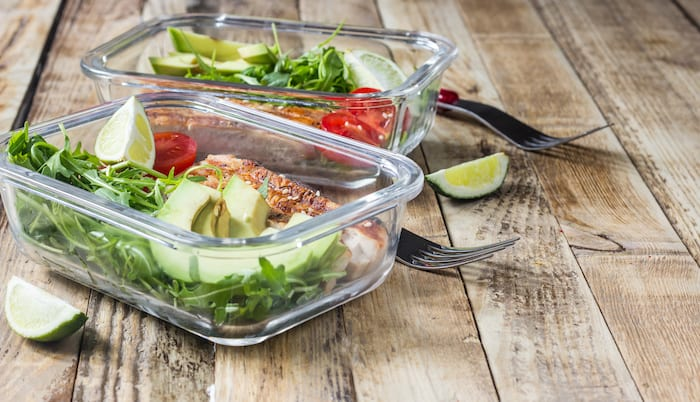 two meal prep containers with chicken, salad and avocados