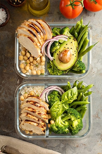 image of two meal prep containers with chicken, rice, green beans, broccoli, and avocado