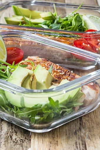 meal prep dishes with chicken, avocado and tomatoes