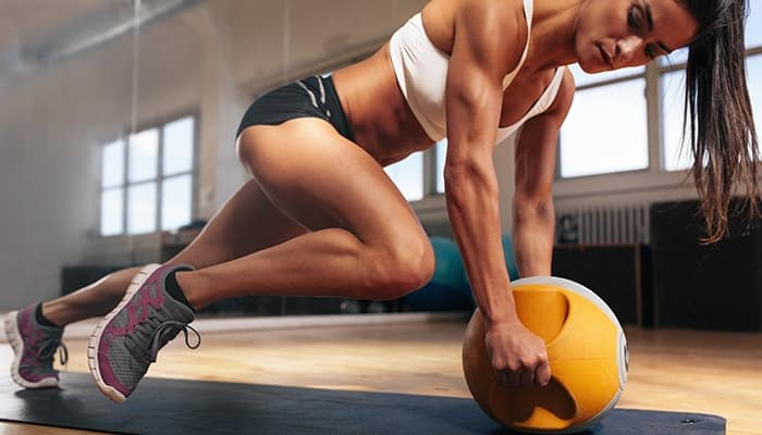 image of a woman doing mountain climbers with a medicine ball