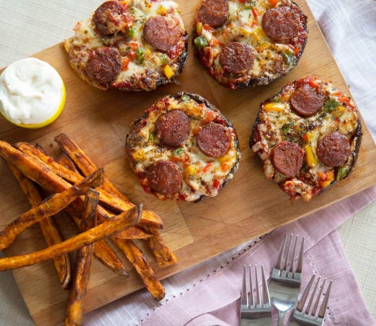 pizza stuffed portobello mushrooms and sweet potato fries on a cutting board