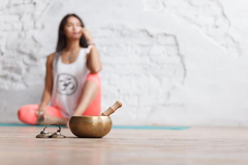 image of a woman on a yoga mat with a singing bowl and chimes