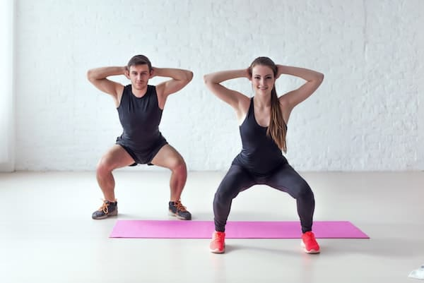 man and woman doing a squat with hands behind their head