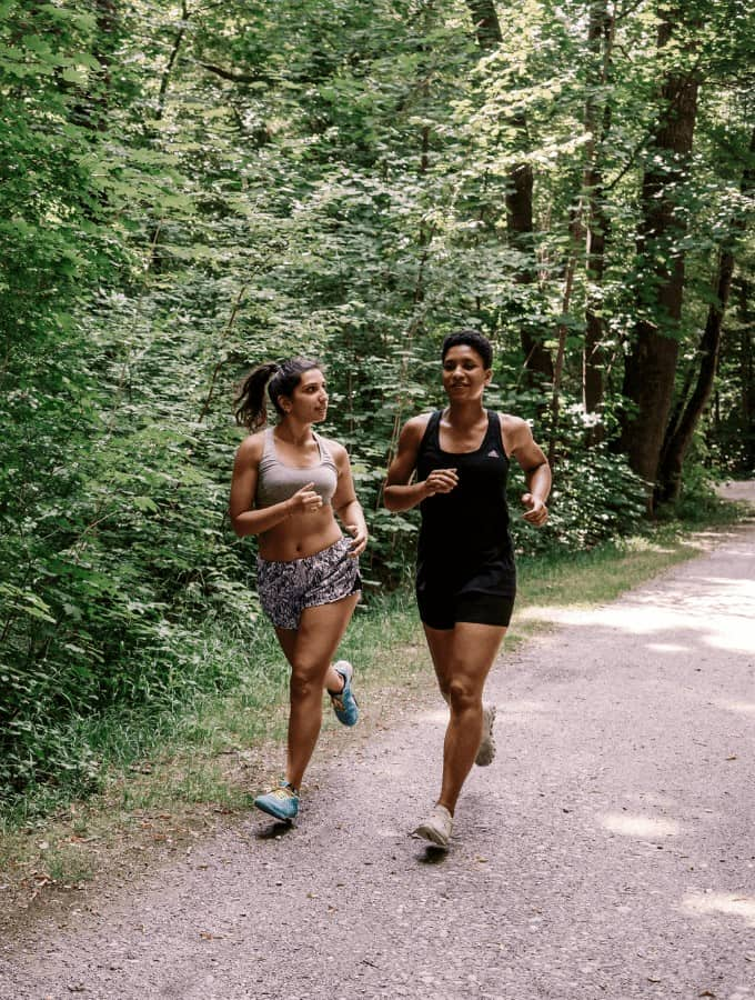 women running on a trail in the woods