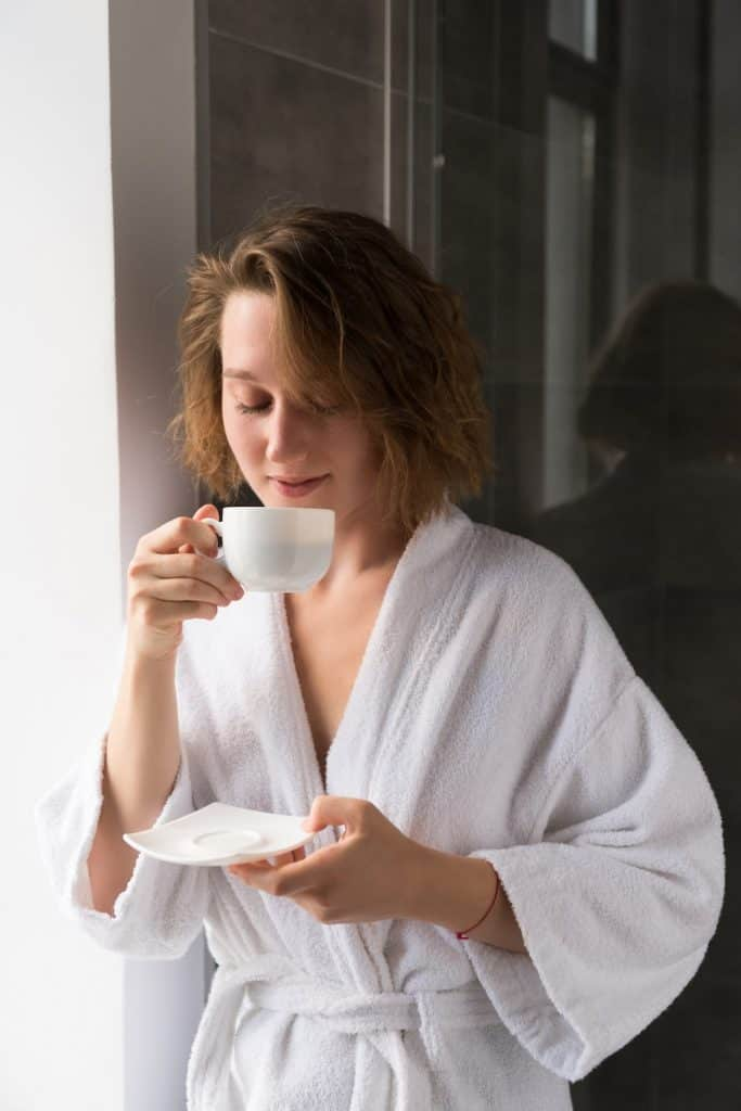 image in a bath robe drinking tea
