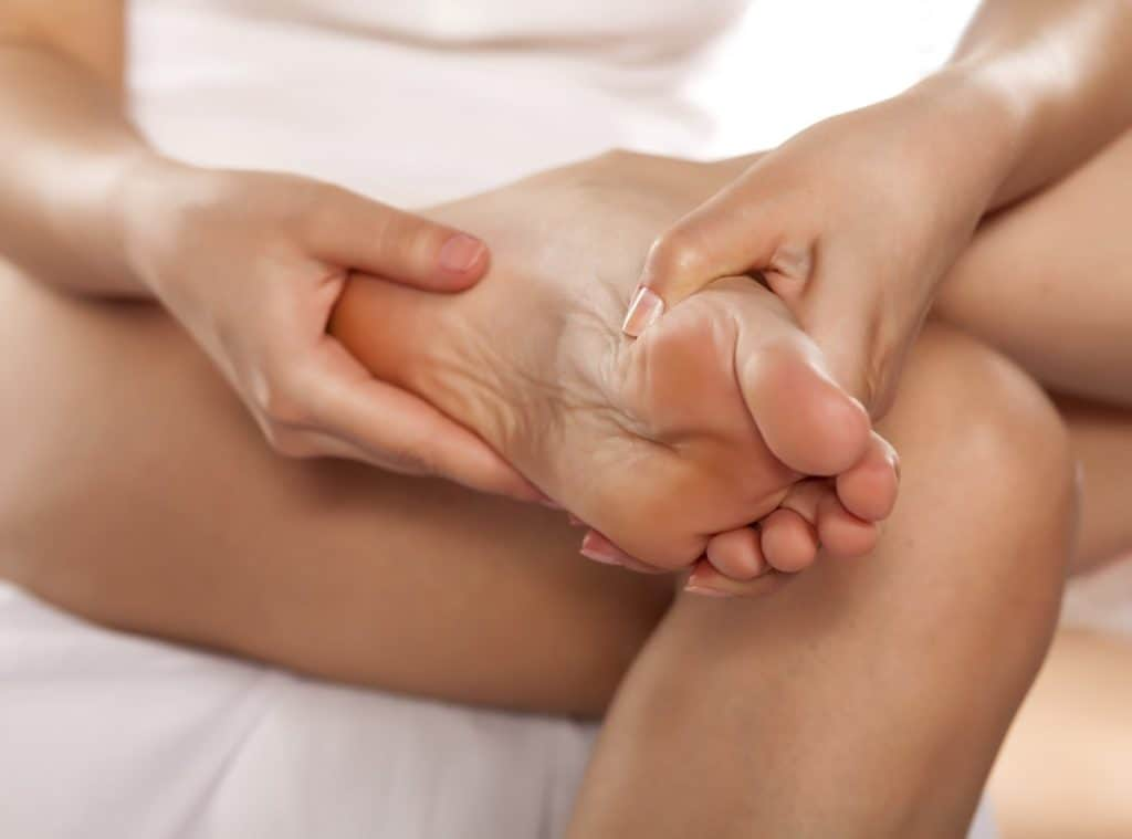 image of woman massaging her feet
