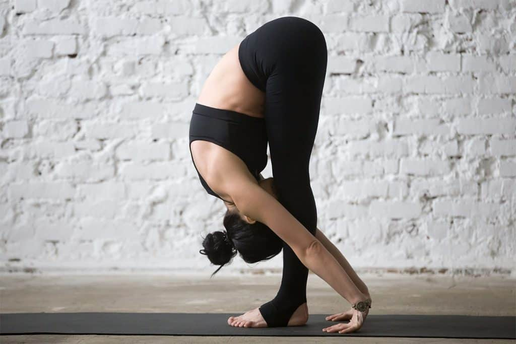 woman doing standing forward fold yoga pose