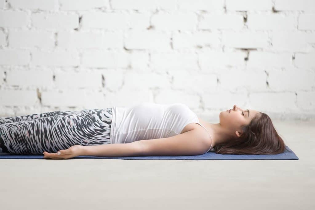 woman laying on the floor in savasana (or corpse pose)