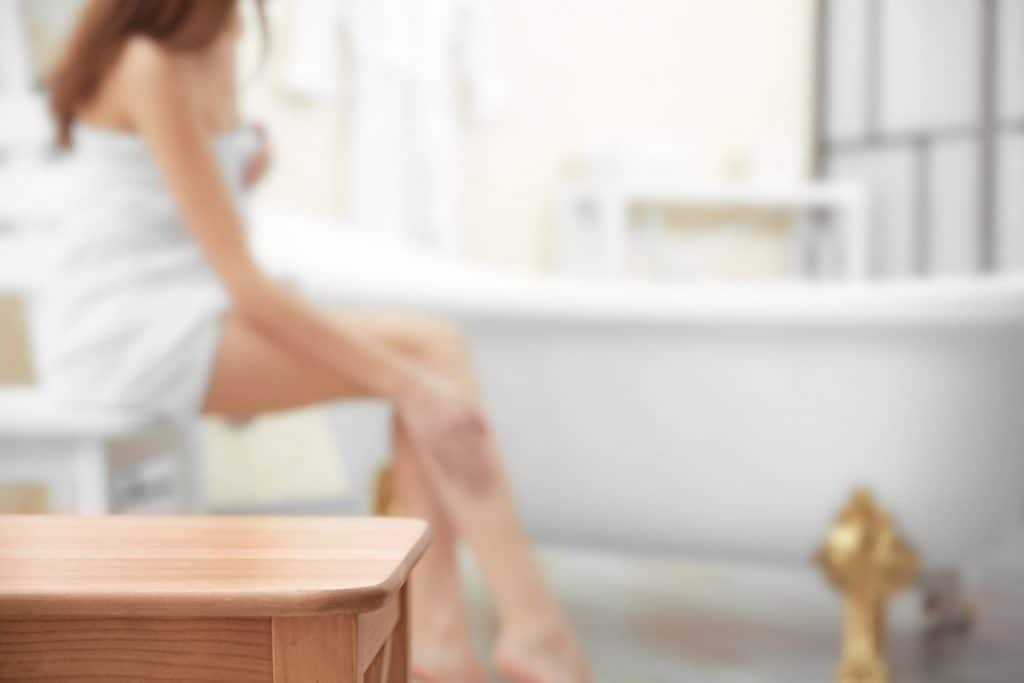 image of a woman sitting by a tub