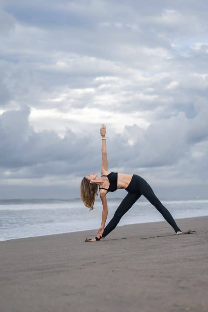 woman doing triangle pose at the beach