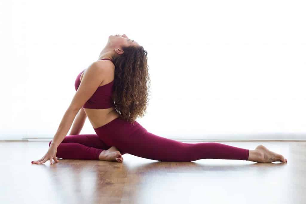 woman doing pigeon pose and looking up