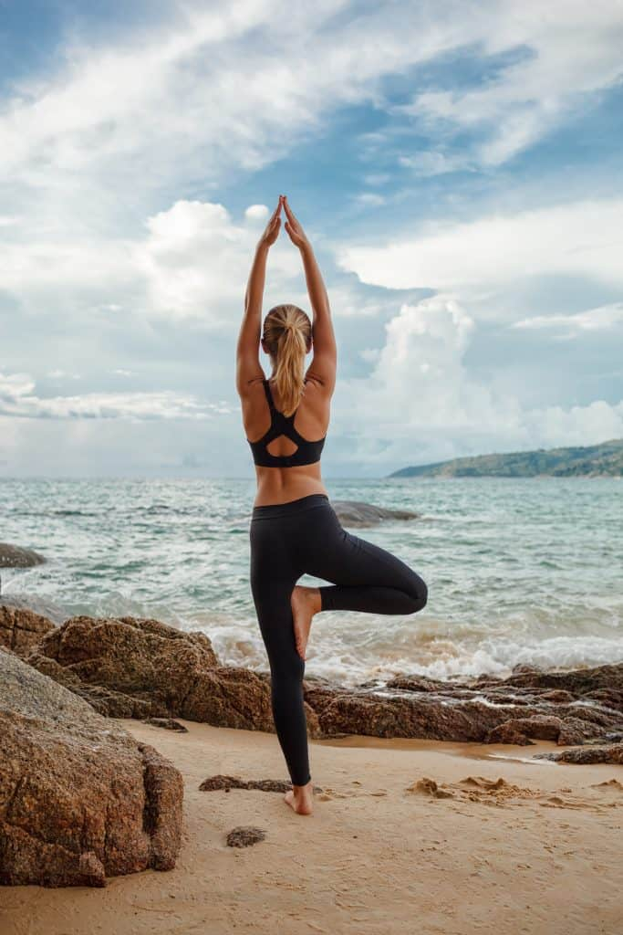woman doing tree pose in front of the ocean