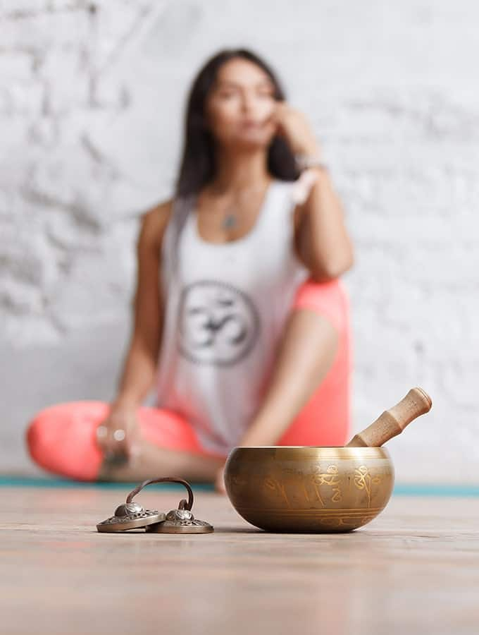 woman sitting on a floor with a singing bowl and chimes