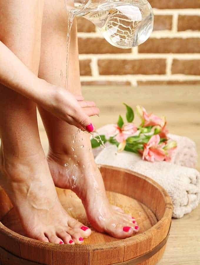 image of a woman putting oil on her feet