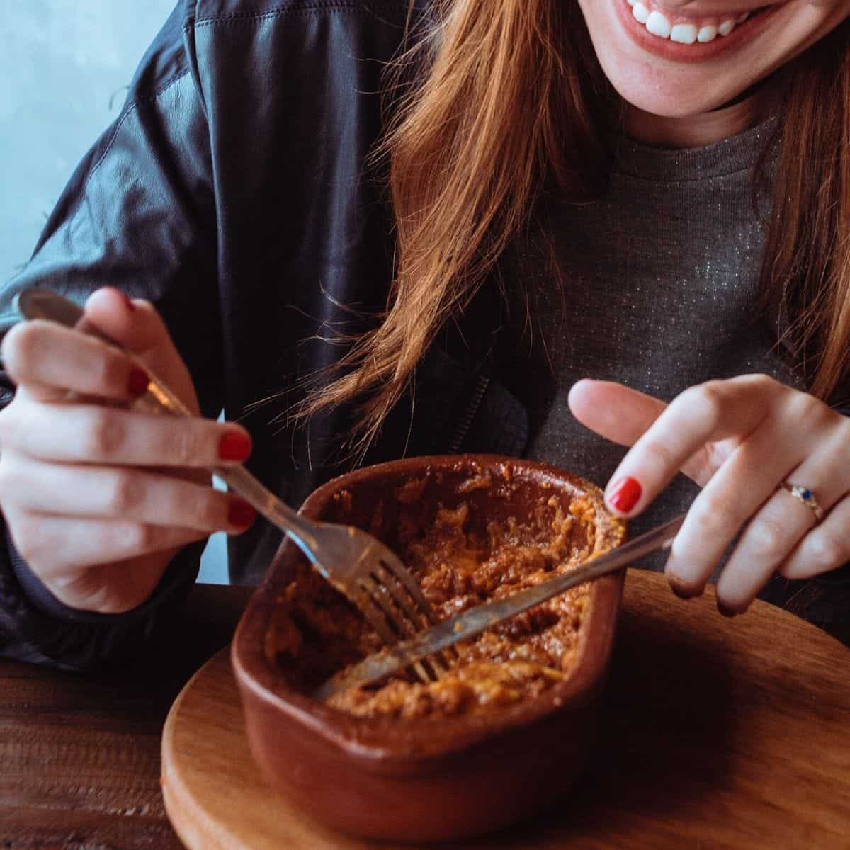 woman eating food out of a bowl
