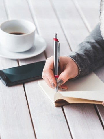 woman writing in a journal with coffee beside her