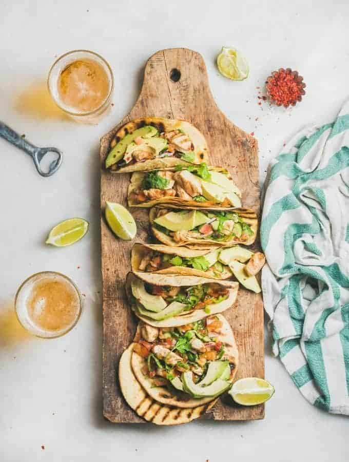 chicken tacos in toasted tortillas on a cutting board