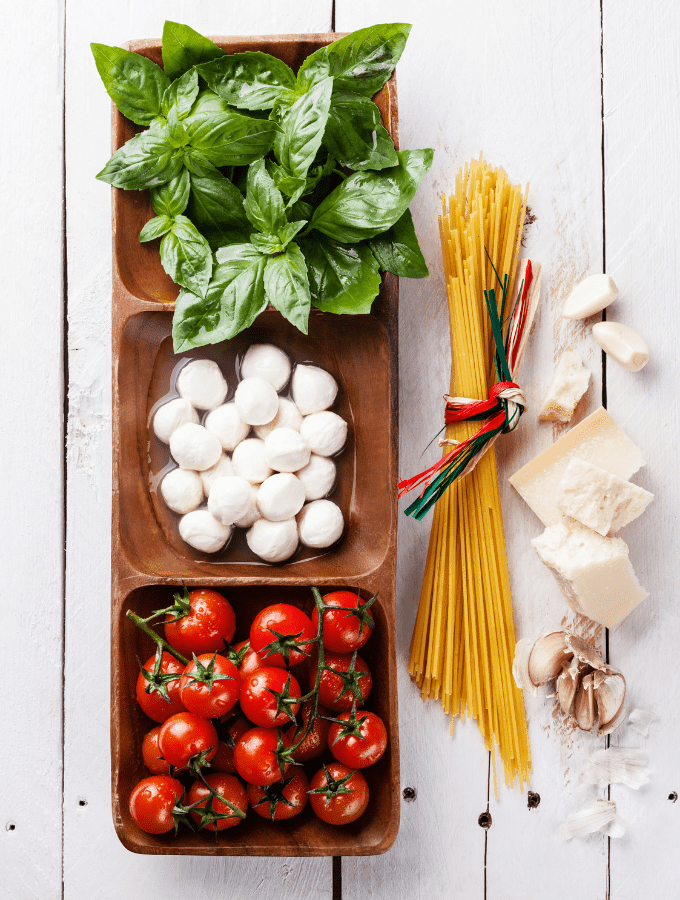 tomatoes, mozzarella, and basil in a try by some spaghetti noodles