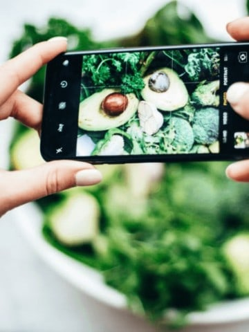 woman taking picture of a vegan keto salad
