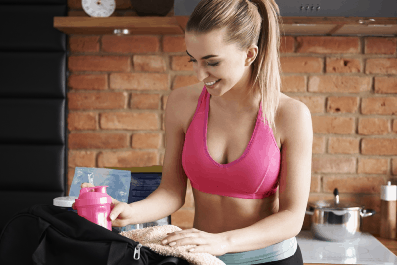 woman packing her gym back with ketone supplements