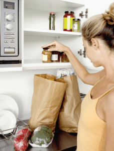 woman putting up groceries in a pantry