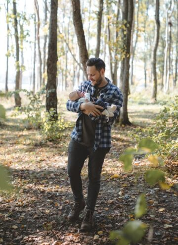 man walking in the woods holding a baby