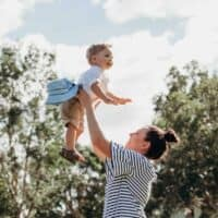 woman tossing her child in the air smiling