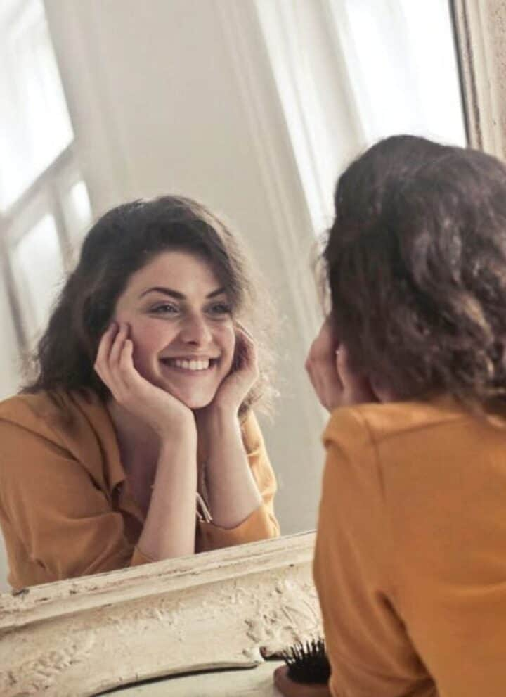 woman looking at herself in the mirror – collagen peptides