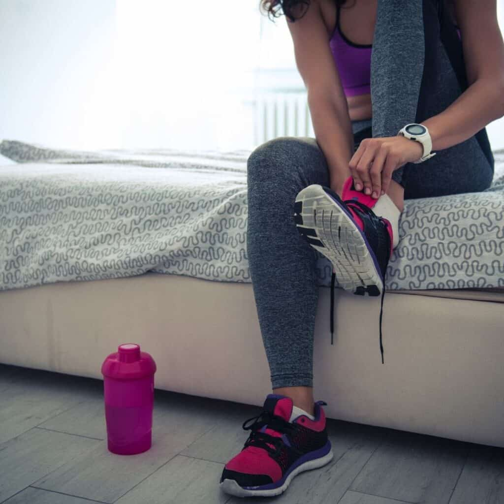 woman sitting on her bed putting on shoes