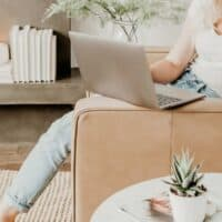 woman sitting on a couch with a laptop looking for the best digital products for bloggers