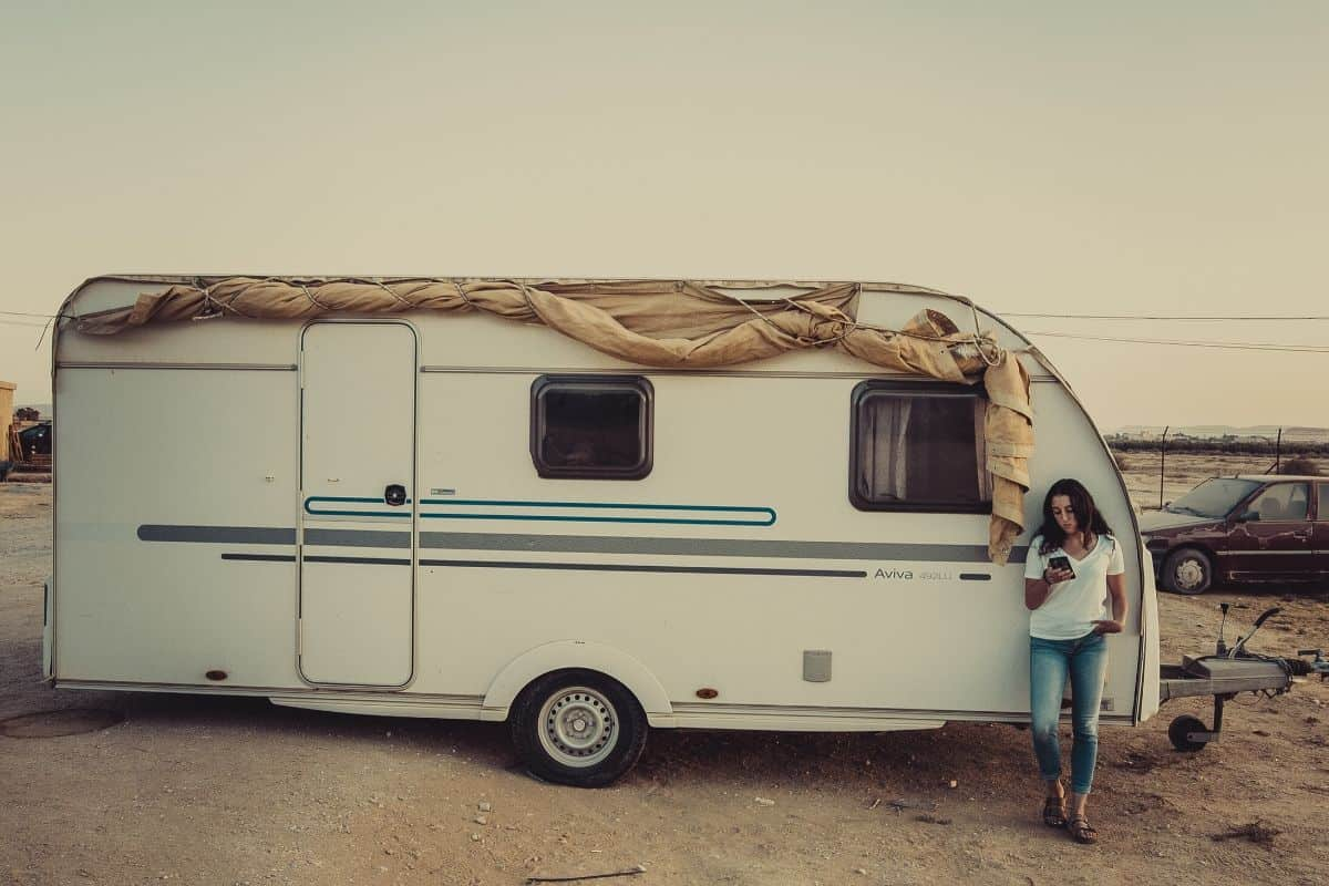 woman outside of a bumper pull rv that she's full-time rv living in
