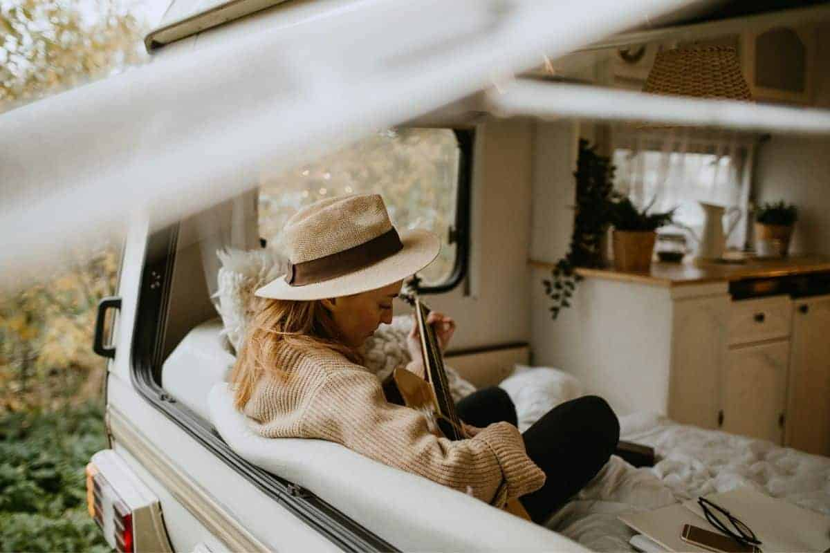 woman sitting on the couch playing a guitar in her driving rv where she's full-time rv living
