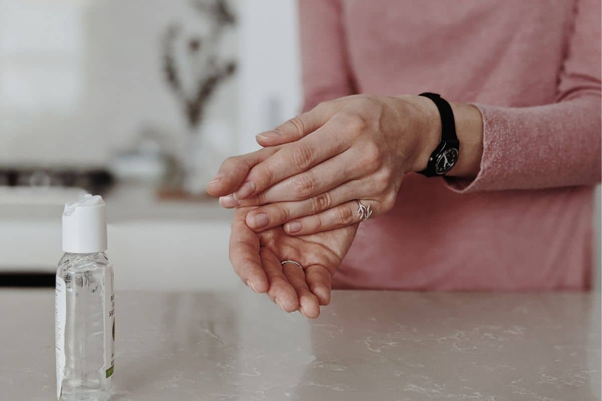 woman putting alcohol-based hand rub on her hands