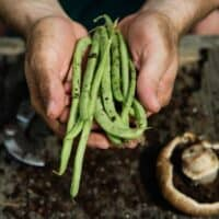 man holding green beans in his hands