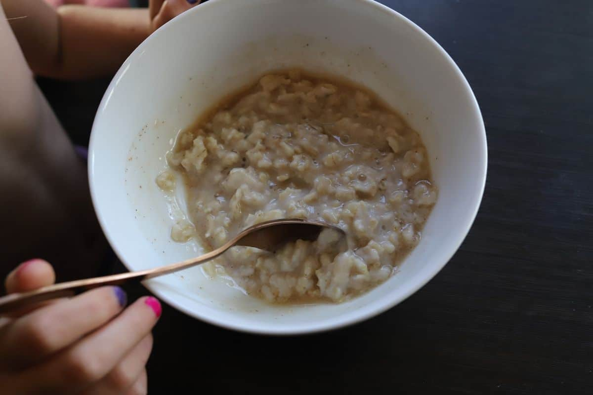 little girl eating stovetop oatmeal with quaker oats with cinnamon