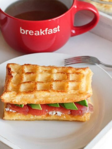 chaffle breakfast sandwich on a plate with a cup of coffee