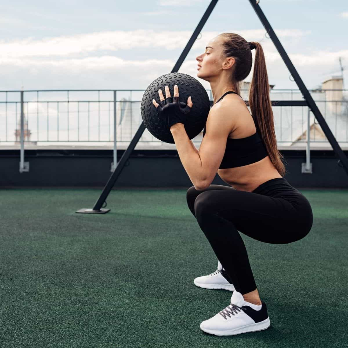 woman squatting with a medicine ball