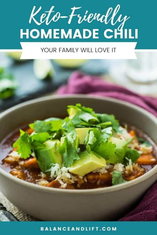 keto friendly chili in a bowl topped with avocado and parsley