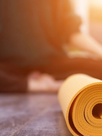 woman meditating behind her rolled up yoga mat